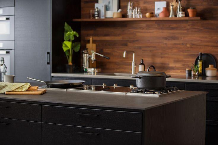Kjøkken med kjøkkenøy er blitt veldig populært! Kjøkkenet på bildet har vår kjøkkendør Metro i eik svartbeiset utførelse. Igjen er det de flotte materialvalgene som gjør hele opplevelsen. Kjøkkenets rustfrie oppvaskbenk og blandebatteri passer veldig bra med den svartbeisede kjøkkendøren. Benkeplaten i grå keramikk på kjøkkenøyen er den siste biten som binder sammen kjøkkenet på en smakfull måte.