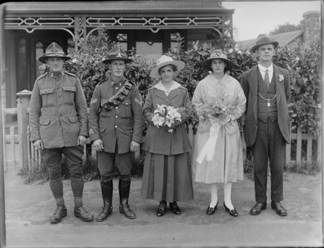 Unidentified wedding party portrait in front of a house with veranda, two men in army uniform, women holding flowers, probably Christchurch region