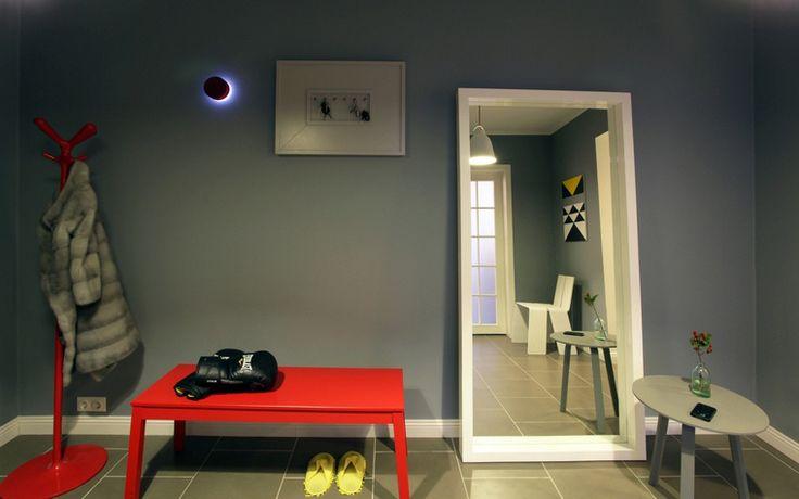 <p>Автор проекта:   MORE DECORE Interior Design & Decoration</p> <p>Серые стены и пол минималистичной прихожей стали отличным фоном для яркой дизайнерской мебели: белого стула-оригами, красной банкетки и забавной вешалки. </p>