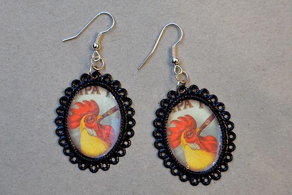 Earrings made of ornate oval-shaped frames and pictures of roosters. http://www.minka.fi/korvakorut-kehyskorvakorut-c-36_104.html
