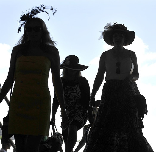 Three women walk around Pimlico Race Course before the 136th Preakness.