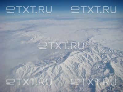 Снежные горы, облака, небо. Красивый вид из самолета.