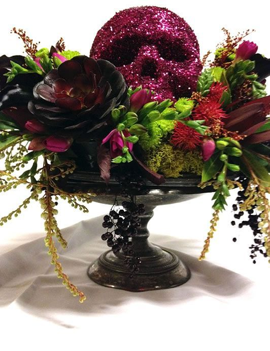 A simple floral display plants in shades of purple, green and black. Placed on a black pedestal and topped with a glittering skull. Your fashionista friends will be impressed.