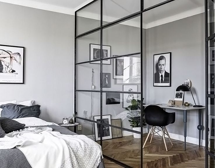 Love the black framed glass partition in this beautiful bedroom/workspace
