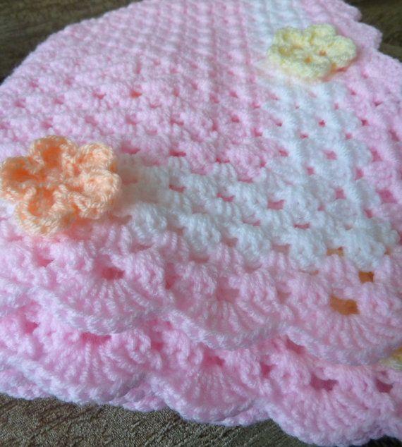 Esta manta cochecito o cuna de tamaño se hace con hilo DK rosa pálido suave en un patrón de puntadas tradicional de la abuela. Una banda blanca
