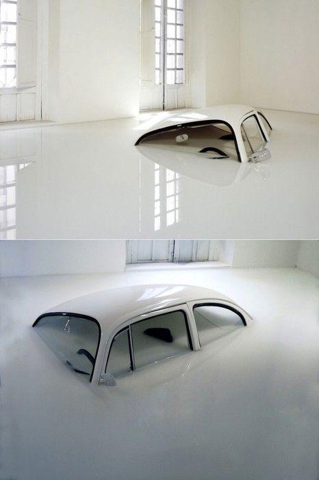 Ivan Puig découpe un morceau de la voiture pour donner l'impression qu'elle coule dans le sol de la galerie.