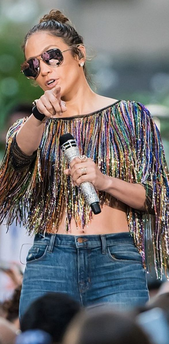 Who made  Jennifer Lopez's rose gold aviator sunglasses, beaded fringe top, blue jeans, pumps, and black jewelry?