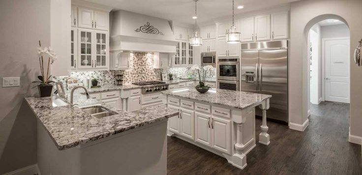 A dream kitchen, with grey granite countertops, glass-door cabinets, an arabesque tile backsplash and a perfect island with breakfast bar - Regency Park // Flower Mound, TX // Huntington Homes // Plan 3970