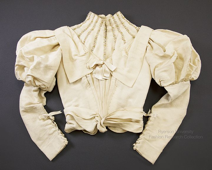 Cream corded silk bodice with high neckline, extended sailor collar and gigot sleeves with ribbon closure at cuff, front hook and eye closures, cream satin bow at chest. Pink, green, blue and cream vertical beaded trim at neckline, cotton interior lining with boning, self-fabric asymmetrical belt, c.1890-1895. FRC1999.06.006