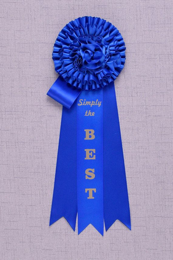 Simply The Best- Nobody does it better! The recipient of this prize is Blue Ribbon all the way. This blue ribbon will make all the other blue ribbons pale in comparison. Deep royal blue luxuriously pleated pom pom rosette with streamers and accents fit for a royal- in blue of course.  -5,5 diameter rosette head -9 streamers -14.5 overall -Royal Blue - Simply The Best printed on center streamer with 300 dpi gold print -Gold cord award hanger with separate gold corsage pin included. Wear it…