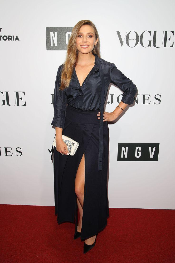 Elizabeth Olsen con blusa y falda azul oscuro de satén, clutch de piel de becerro y zapatos de Dior.