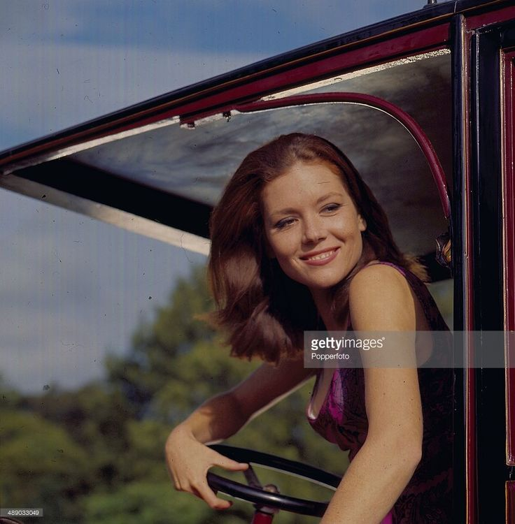English actress Diana Rigg pictured in the driving seat of a vintage car in a scene from the television series 'The Avengers' in 1967.
