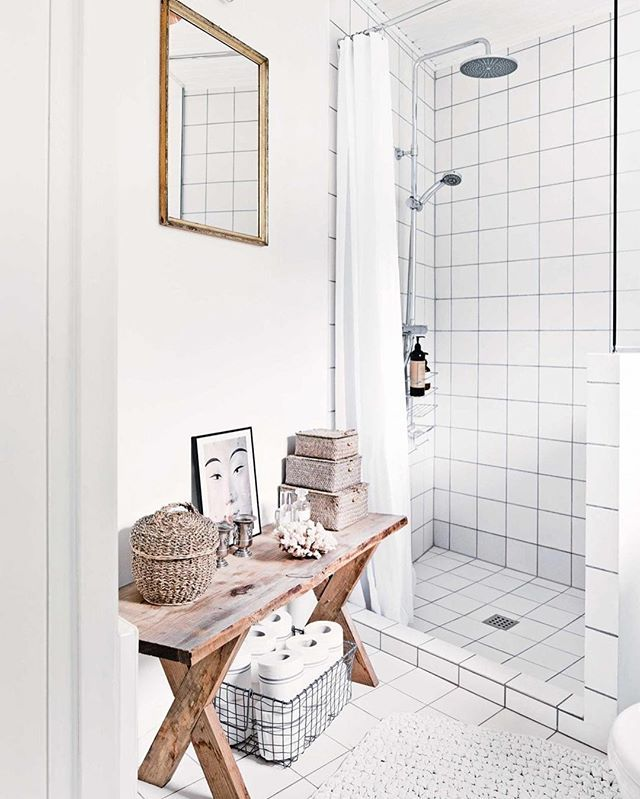 Simple accessories add personality to this small bathroom, with an old bench utilised as storage for wet room essentials. To see more of this Scandi-style home that mixes old with new, hit the link in our bio.  Styling - Luke Foged Photography - Morten Holtum/Living Inside