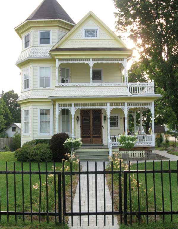 Charming Victorian house with details in glass, screen doors, porch ornamentation, and skirting.