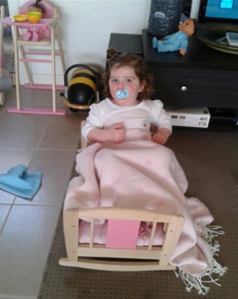 """Cute two-and-a-half-year-old Maddie loves her Pintoy Dolls Cradle – it's super comfy (""""Maybe a little too comfy?"""" questions her Mum). She also adores her Pintoy High Chair and Wheely Bug that are in the background."""