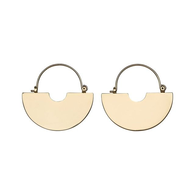 Graphic, statement flat disc hoop earrings crafted in plated brass. The modern hoop shape fastens via metal clasp.