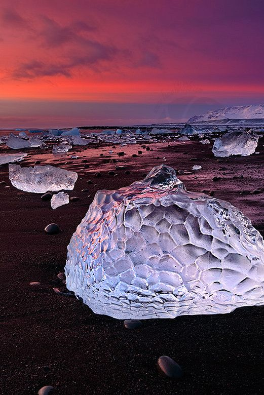 The volcanic rock of Iceland accounts for the black sand, and the ice pieces come from a nearby glacier that runs off into the lagoon.
