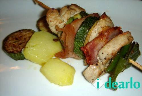 Ingredientes: - Solomillo de cerdo - Cebolla - Calabacín - Pimiento verde italiano - Bacon - Sal - Aceite - Pimienta Elaboración: Cortamos la cebolla y el pimiento en cuadrados grandes, el calabací...