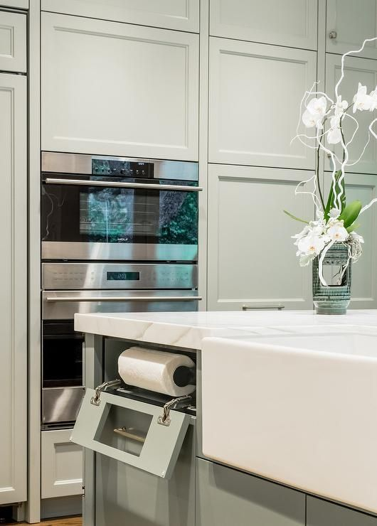 Fitted with a farmhouse sink and a built-in drop down paper towel holder, a gray kitchen island is topped with a marble countertop and positioned beside stacked gray floor-to-ceiling cabinets beautifully framing a stainless steel microwave fixed above a stainless steel oven.