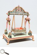 A carved and painted temple cradle (palki) swing, with carved cornices supported on two carved columns on top of four elephants with wooden rods holding a carved settee with cushions on a square wooden base. The cradle size is adjustable as can be seen from the illustration.     47 x 32 x 87 in