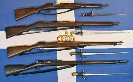 The main arms of the Greek army before WWI, shown over the Royal Greek Battle Flag. (Top to bottom) Model 1903 Mannlicher-Schoenauer Carbine, M1903/14 M-S Infantry Rifle, M1903 M-S Infantry Rifle and M1878 Greek Gras Infantry Rifle.