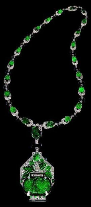 A magnificent Art Deco emerald and diamond necklace, Mauboussin, Paris, circa 1925. Suspending a large pendant with an Oriental flower vase motif, set with carved Columbian emeralds and round diamonds, with black enamel and cabochon, joined by a black enamel loop to a similarly designed emerald, diamond and black enamel chain, mounted in platinum. Numbered, with French hallmarks and maker's mark. #Mauboussin #ArtDeco #necklace