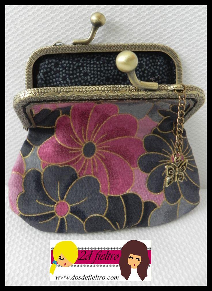 Monedero boquilla metalica cuadrada, con tela exterior de flores en tonos grises, negros y rosas y tela interior negra con puntos grises. colgante mariposa