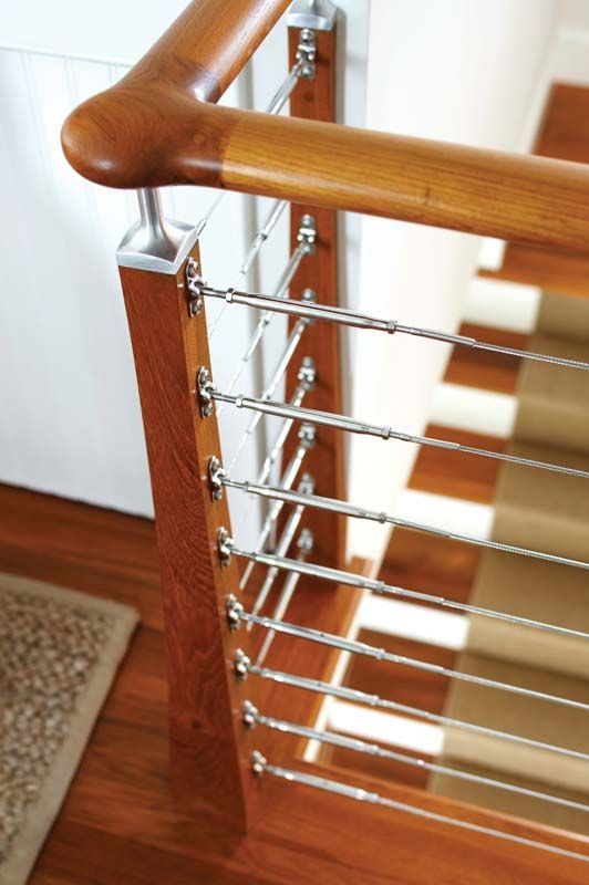 Nautical-inspired teak staircase has horizontal, stainless-steel cable balustrades.