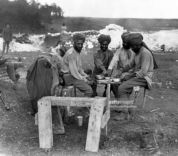 World War One, 1914-1918, Indian soldiers wearing traditional turbans relax around a makeshift dinner table to eat al fresco