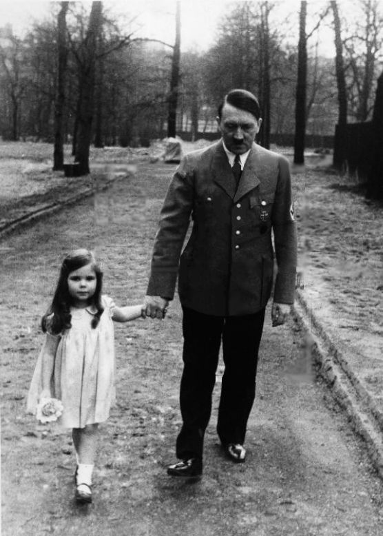 Adolf Hitler on a walk with Helga Goebbels, 1936.  Ain't it sweet?  What is really scary is poor little Helga.  Through no fault of her own, this adorable child was not only born into the heart of the Nazi environment, but murdered by her own Nazi parents in a murder-suicide spurt, 1945.