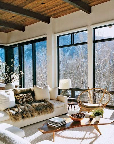 Aerin Lauder's cozy and chic winter home in Aspen, Colorado, decked out with faux fur, white and ivory sofa, chair, lamp, and carpet, natural and organic wood touches and sweeping mountain views.