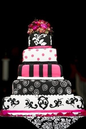 A bold pink, black, and white square wedding cake featuring polka dots, damask, and scroll patterns.