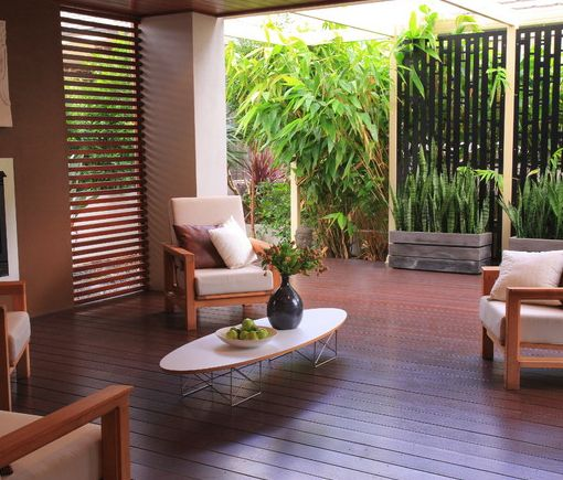 Create a Bali style privacy screen with wooden slats and bamboo plants.