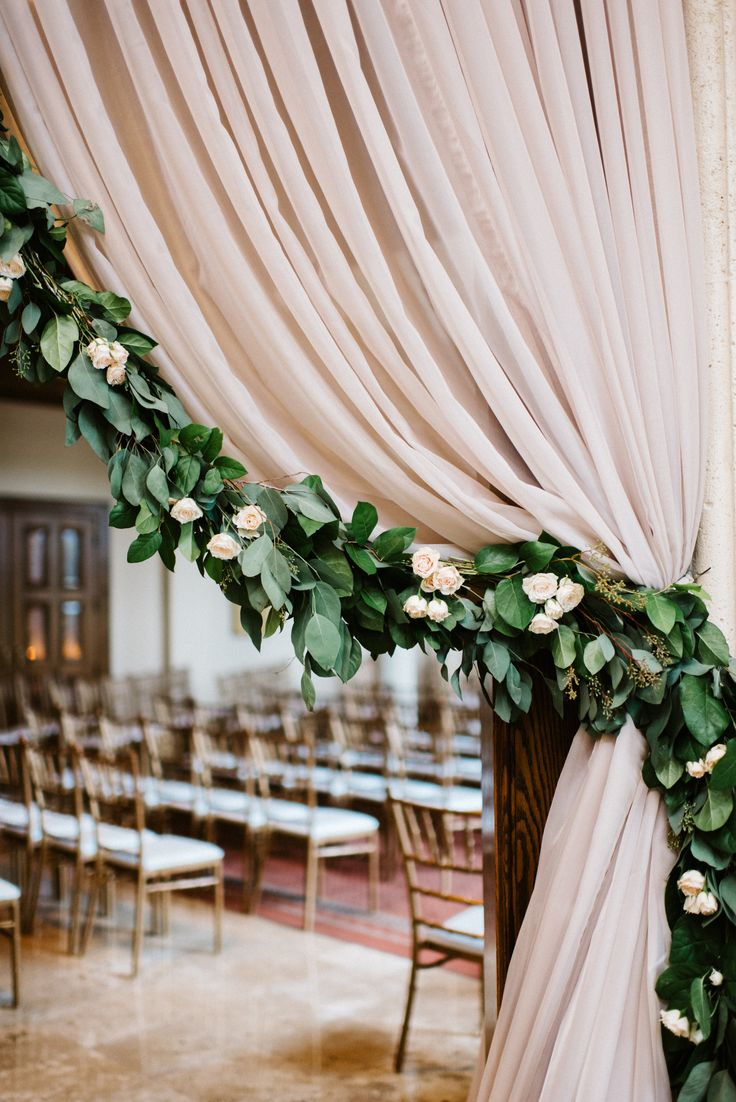 wedding entryway draping detail featuring full garland of lemon leaf and seeded suclayptus, peppered with white and ivory spray roses.