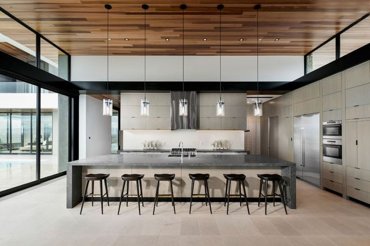 In this modern kitchen, a large island creates plenty of counter space and provides seating for six people. Clerestory windows line each side of the main living room/kitchen and help to make the roof appear to float above the space.