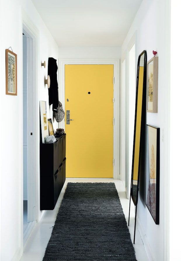 Bright, sunny yellow door in the hallway. A Danish home is given a fresh, monochrome make-over. Tia Borgsmidt.