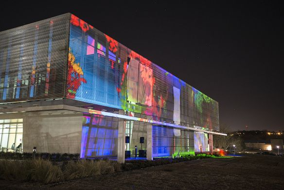 A key feature of the building is the screen walls surrounding two sides of the exterior. This south screen wall doubles as a backdrop for projector shows and movies. This projector show produced by GuruStu launched the building's grand opening.