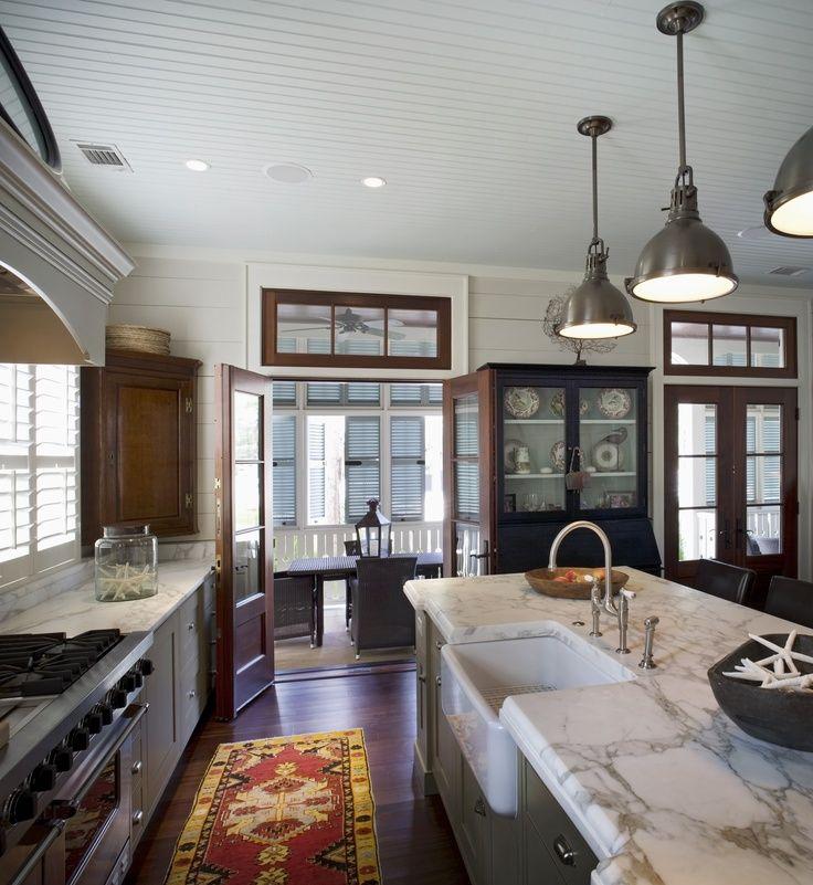 homey kitchen showcasing medium brown flooring/trim, bronze lighting fixtures, marble counters & enhanced with a pretty Oriental runner