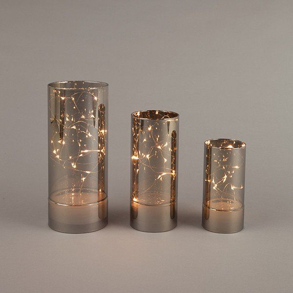 """S/3 smoke glass hurricane with micro LED light string, warm white, 4in spacing, silver wire, no timer. Batteries not included. 1 pc Each 2.75""""x5.9"""" w/8L, requires 2 AAA; 3.14""""x7.87"""" w/10L,requires 2 A"""