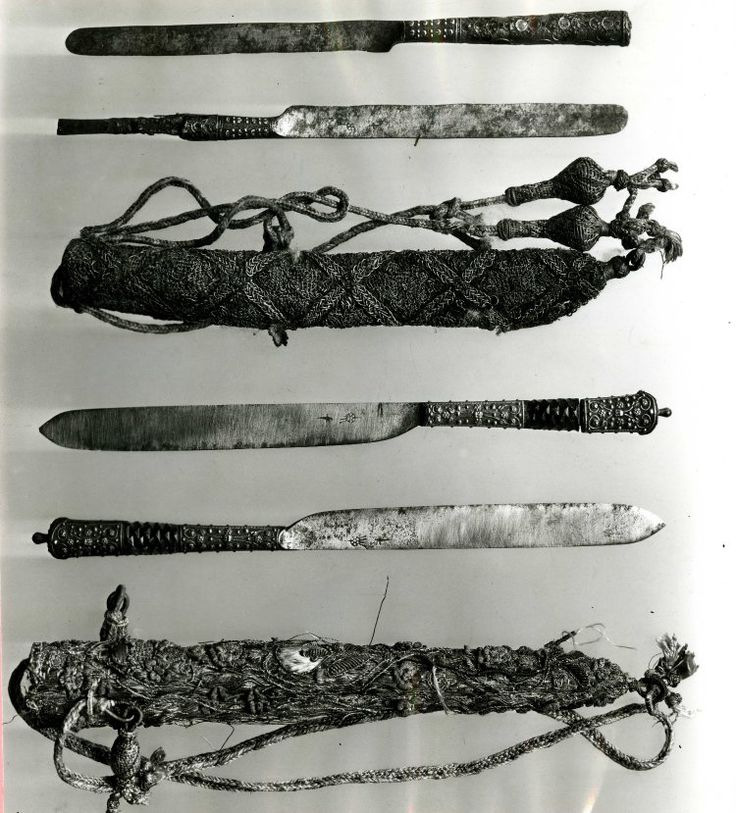 Pair of wedding knives; steel blades, rounded at the end and stamped with the maker's mark; the handles are of silver ornamented with filigree and enamelled green and lilac; one handle is damaged; the sheath is embroidered with silver and gold with lozeng