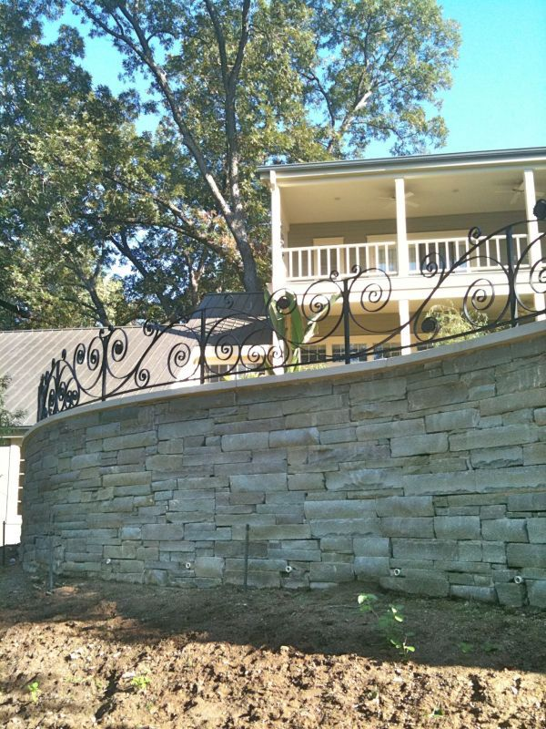 Organic Curved Wrought Iron Fence On Stone Wall For Pool Enclosure.