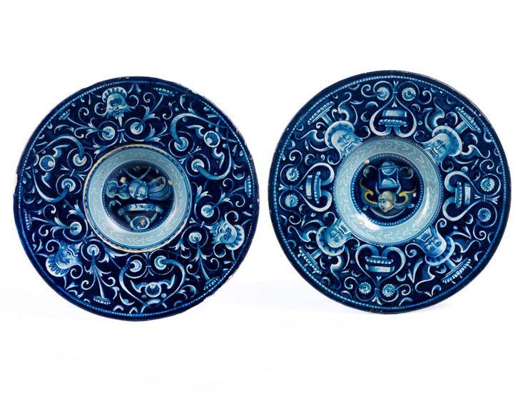 Paar kleine, tief gemuldete Teller auf kurzem Fußring mit breiter Fahne. Im Spiegel sind Trophäen zu sehen und bei einem der Teller ein Band mit der Datierung ...