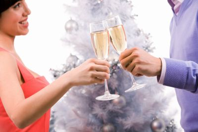 Close-up of couple cheering up with champagne flutes