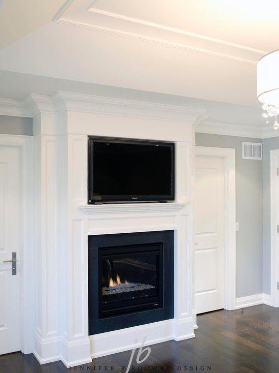 SallyL: Elegant wood paneled fireplace with builtin tv. Dark hardwood flooring and tray ceiling. ...