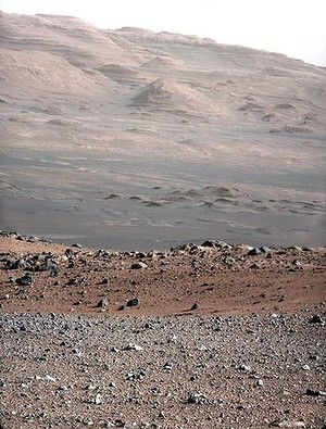 The gravelly area around Curiosity's landing site is visible in the foreground. Farther away, about a third of the way up from the bottom of the image, the terrain falls off into a depression (a swale). Beyond the swale, in the middle of the image, is the boulder-strewn, red-brown rim of a moderately-sized impact crater. Farther off in the distance, there are dark dunes and then the layered rock at the base of Mount Sharp. Some haze obscures the view, but the top ridge, depicted in this…