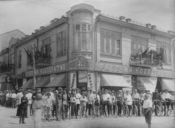 1927.Участники юношеского велопробега(велосипеды с красными флажками) . На втором плане - очередь мужиков в винный магазин.