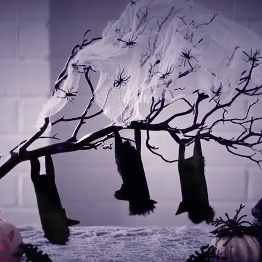 Themed centerpieces are great for holiday parties, but they take up valuable space on the table, leaving less room for food. A perfect solution to this dilemma is a floating centerpiece, which hangs above the table. For this Halloween floating centerpiece, a gnarled branch with sleeping bats appears to be suspended in midair, adding to the decoration's spook factor.