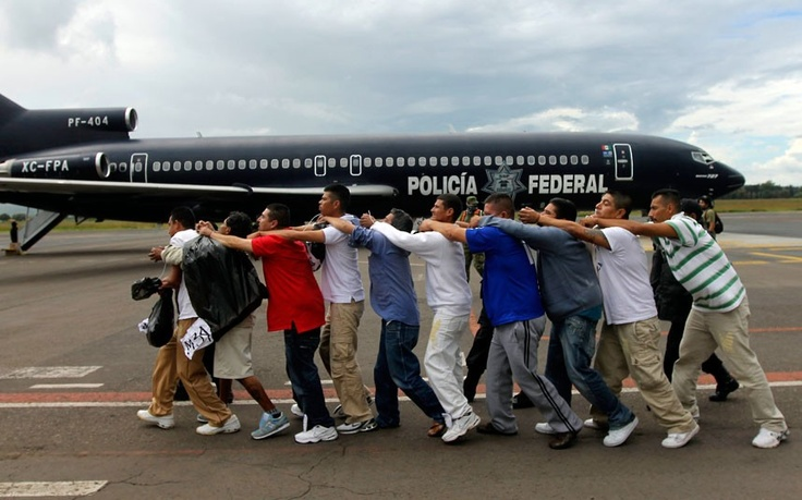 Federal policemen escort a group of prisoners toward a plane bound for an undisclosed location at the Morelia's international aiport in Mexico