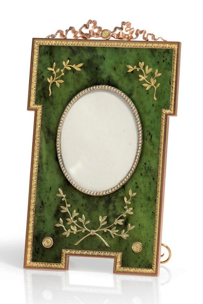 A Three-Color Gold-Mounted Nephrite Photograph Frame Marked Fabergé, with the workmaster's mark of Henrik Wigström, St. Petersburg, 1896-1908, scratched inventory number 9812 Rectangular, with outset upper corners and bracket feet, the translucent nephrite panel mounted with gold sprigs of berried laurel, centering a pearl-set oval aperture, all within a chased acanthus leaf border, surmounted by a tied ribbon crest, with gold scroll strut,