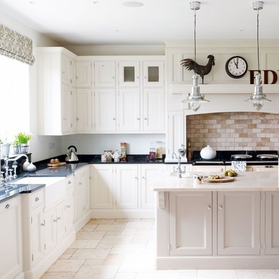 Pale-coloured stone flooring against white-painted cabinetry combines to create a classic, country look